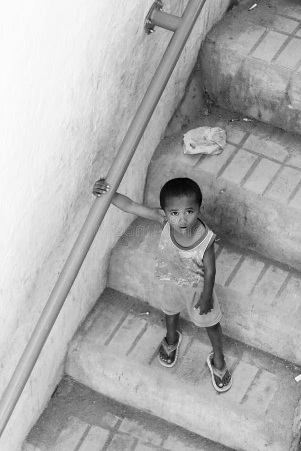 Il bambino locale discende una scala del villaggio da solo in Flores fotografia stock libera da diritti