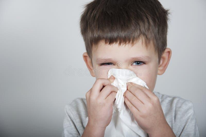 Il bambino malato soffia il suo naso in un fazzoletto fotografia stock libera da diritti