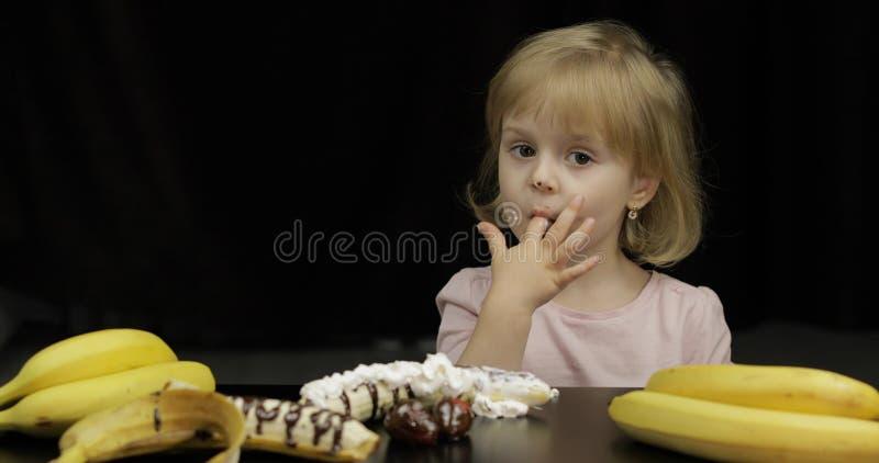 Il bambino mangia il cioccolato fuso e la panna montata Fronte sporco fotografia stock