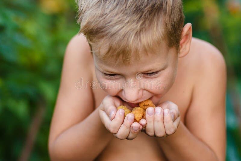 Il bambino mangia i lamponi gialli fotografia stock libera da diritti