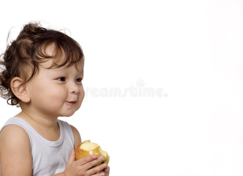 Il bambino mangia una mela. immagine stock