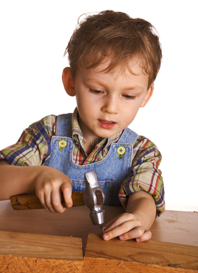 Il bambino martella un martello in chiodi immagine stock libera da diritti