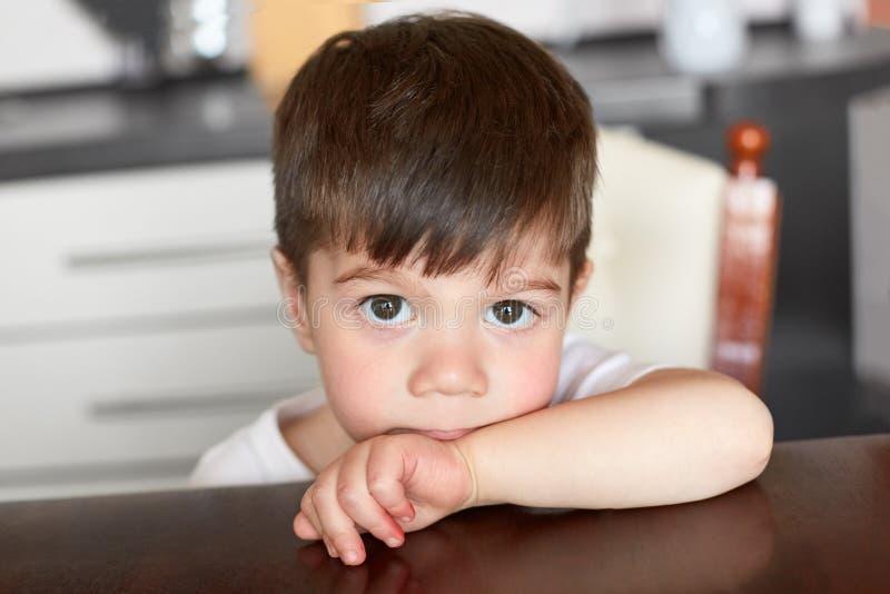 Il bambino maschio osservato piccolo buio dà una occhiata a sopra il bordo della tavola, aspetta la cena, posa contro il fondo va immagini stock