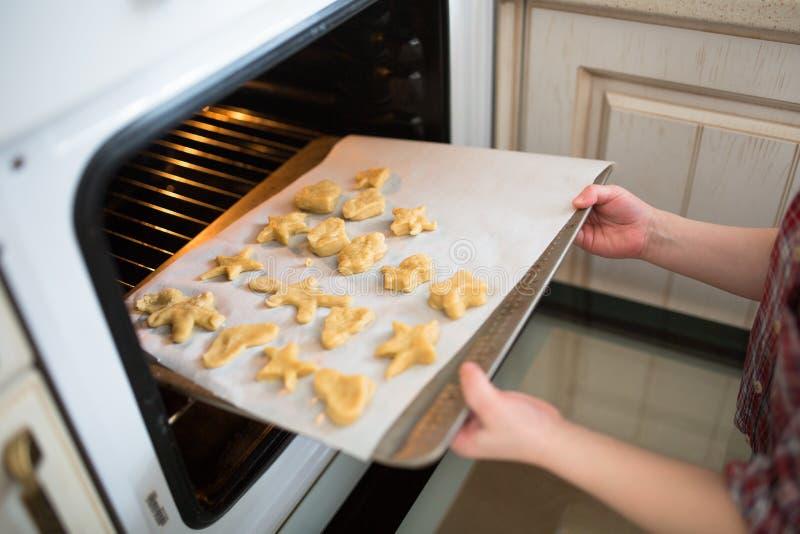 Il bambino mette nei biscotti del forno, bambini indipendenti, casua immagine stock