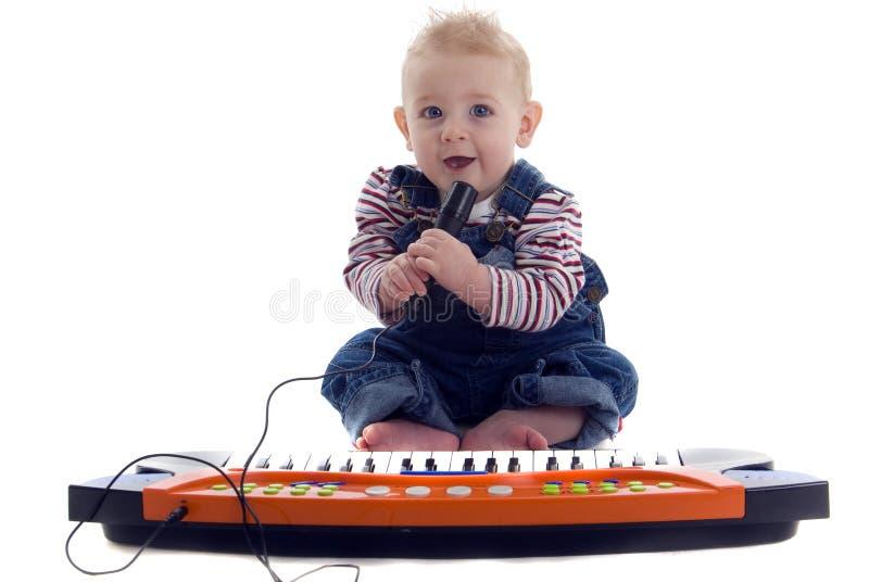 Il bambino musicale gioca la tastiera e canta il karoke immagine stock libera da diritti
