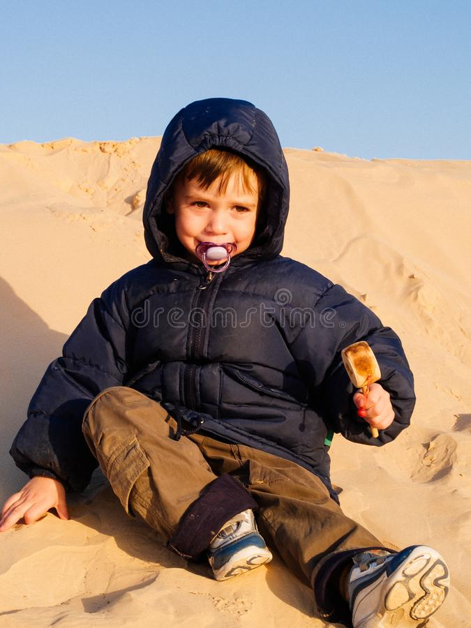 Il bambino nel deserto del Sahara gioca con la sabbia delle dune, tou immagine stock
