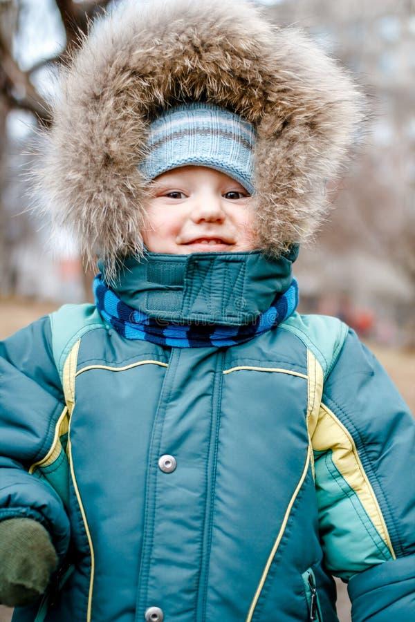 Il bambino nel rivestimento con pelliccia lanuginosa all'aperto fotografie stock
