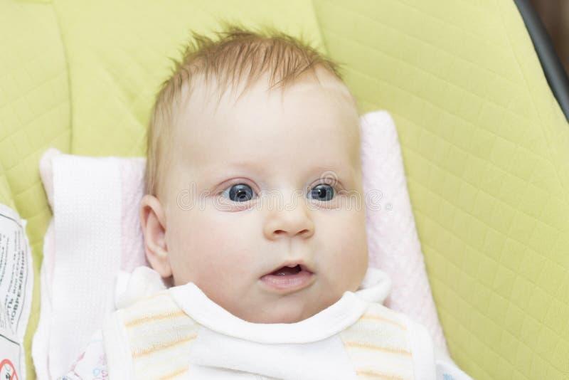 Il bambino nel sedile del bambino immagine stock