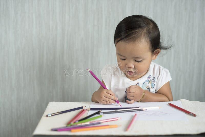 Il bambino/neonata asiatici sta divertendosi l'apprendimento utilizzare le matite fotografia stock