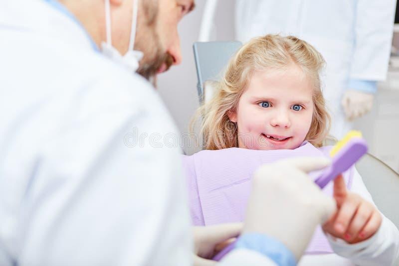 Il bambino ottiene i consigli di cure odontoiatriche dal dentista pediatrico fotografie stock libere da diritti