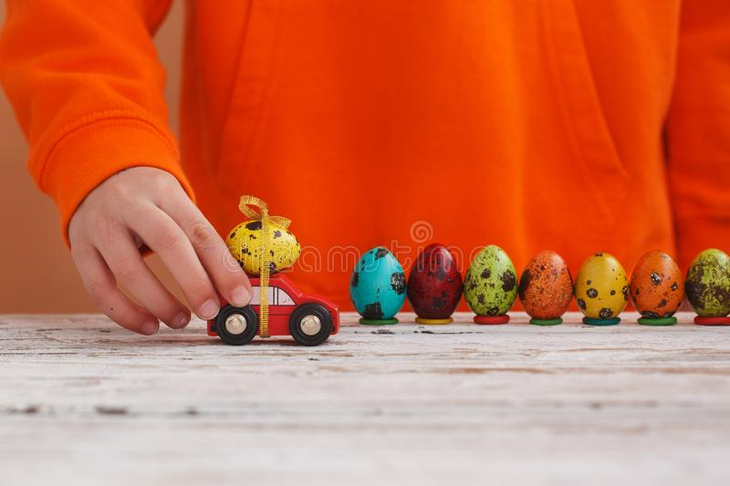 Il bambino passa il gioco dell'uovo di Pasqua sull'automobile su fondo arancio Concetto di festa immagini stock libere da diritti