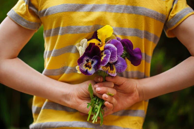 Il bambino passa la tenuta del fiore di viole del pensiero del mazzo Vista posteriore Fuoco per i fiori immagine stock