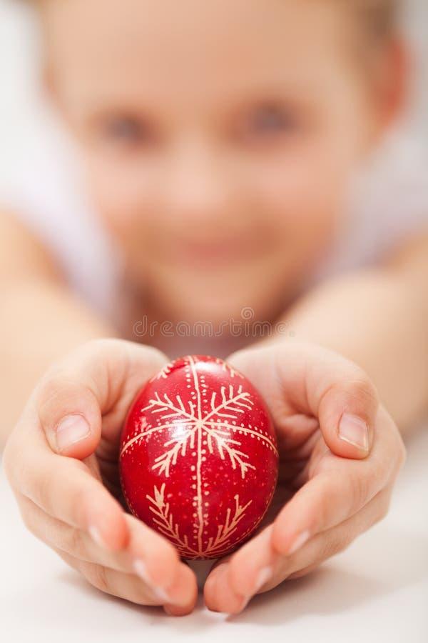 Il bambino passa la tenuta dell'uovo di Pasqua decorato tradizionale immagine stock
