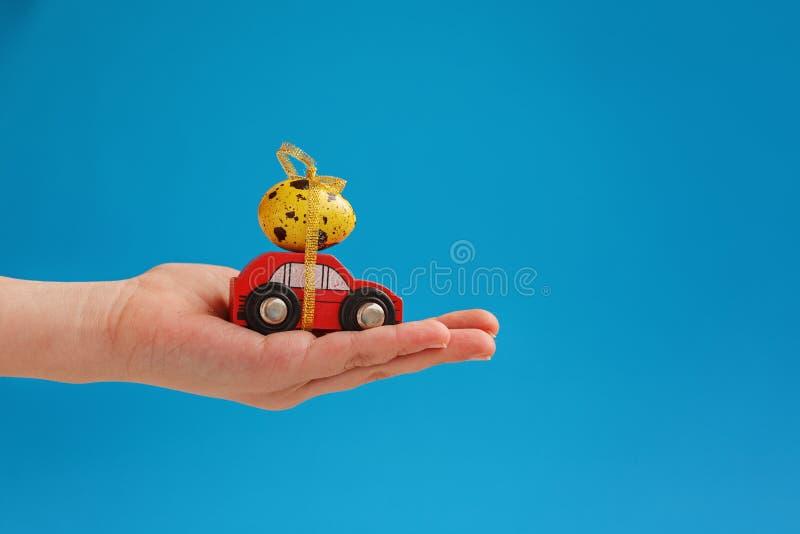 Il bambino passa la tenuta dell'uovo di Pasqua sull'automobile Concetto di festa immagine stock