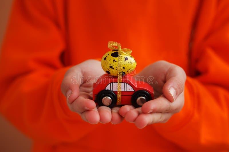 Il bambino passa la tenuta dell'uovo di Pasqua sull'automobile su fondo arancio Concetto di festa immagine stock libera da diritti