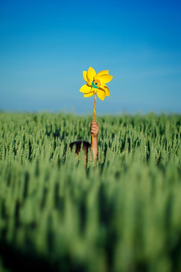 Il bambino passa la tenuta della girandola gialla contro cielo blu ed il campo verde fotografia stock