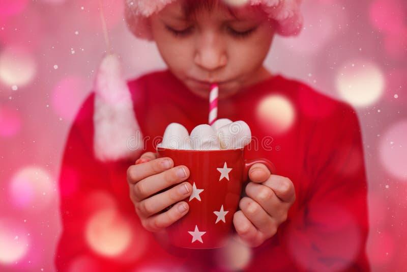 Il bambino passa la tenuta della tazza rossa di cacao o di cioccolato caldo con la caramella gommosa e molle Concetto di Natale immagini stock