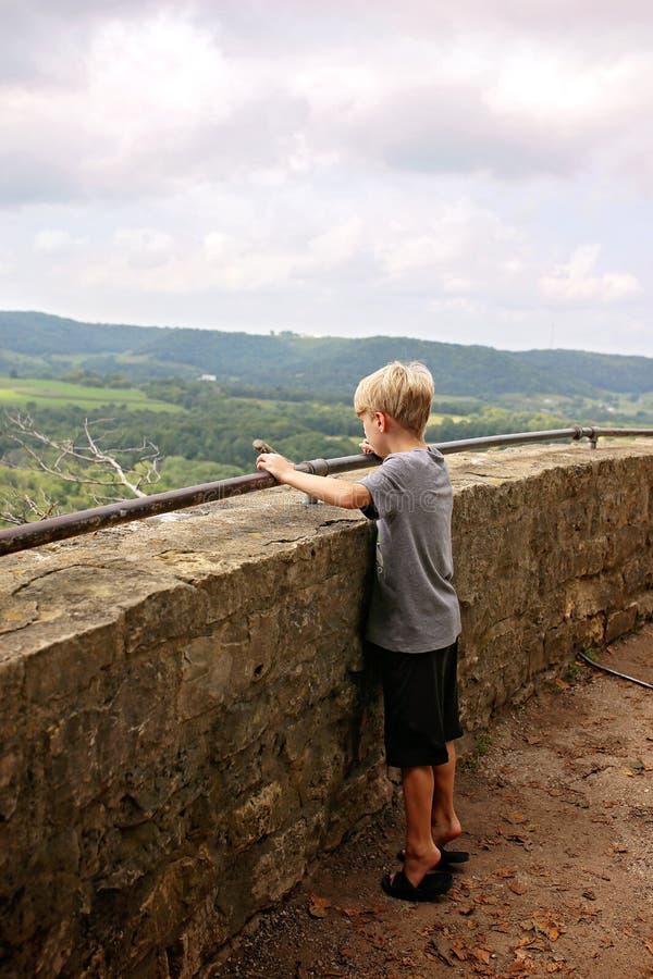 Il bambino piccolo che sta sulle punte dei piedi che esaminano sceniche trascura il Cli fotografia stock libera da diritti