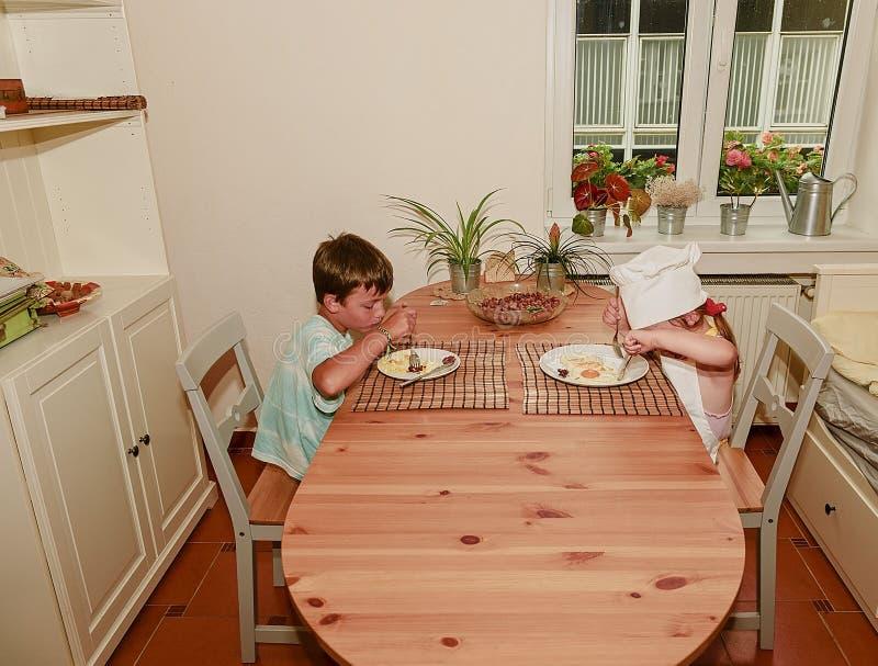 Il bambino piccolo e la ragazza hanno uno spuntino I fratelli germani mangiano il prosciutto e le uova Famiglia e concetto di inf immagine stock libera da diritti