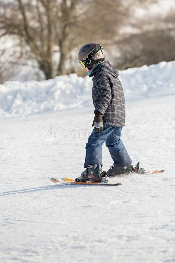 Il bambino piccolo nella passamontagna ed in casco impara la corsa con gli sci immagine stock libera da diritti
