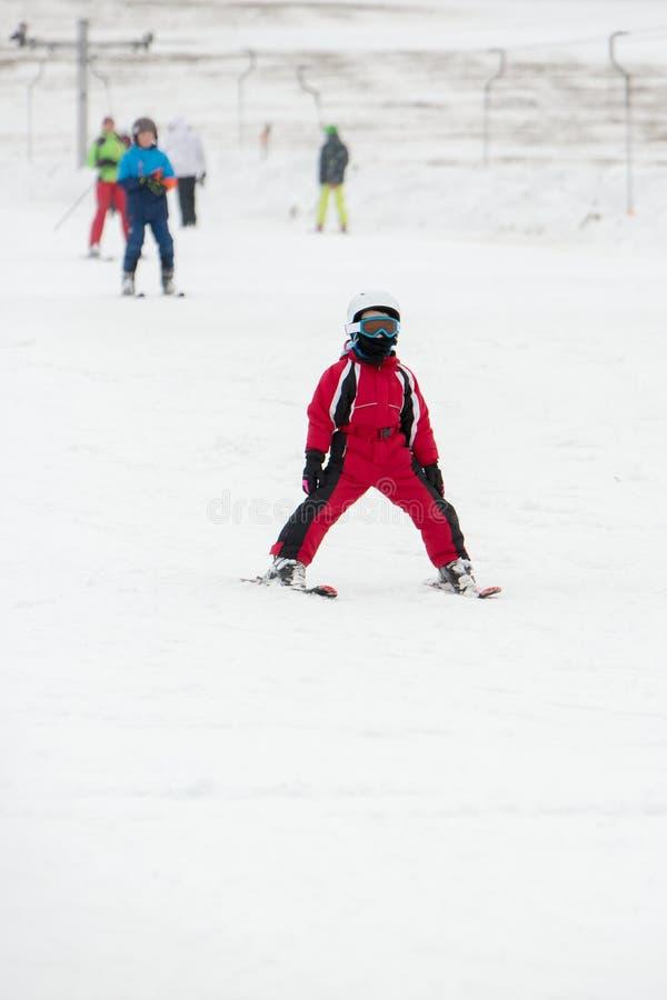 Il bambino piccolo nella passamontagna ed in casco impara la corsa con gli sci immagini stock