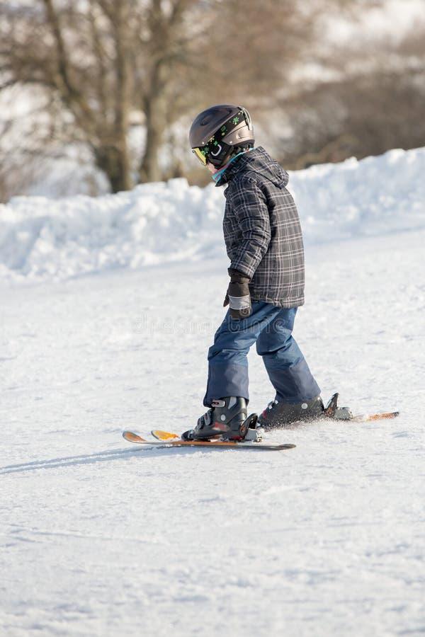 Il bambino piccolo nella passamontagna ed in casco impara la corsa con gli sci fotografia stock