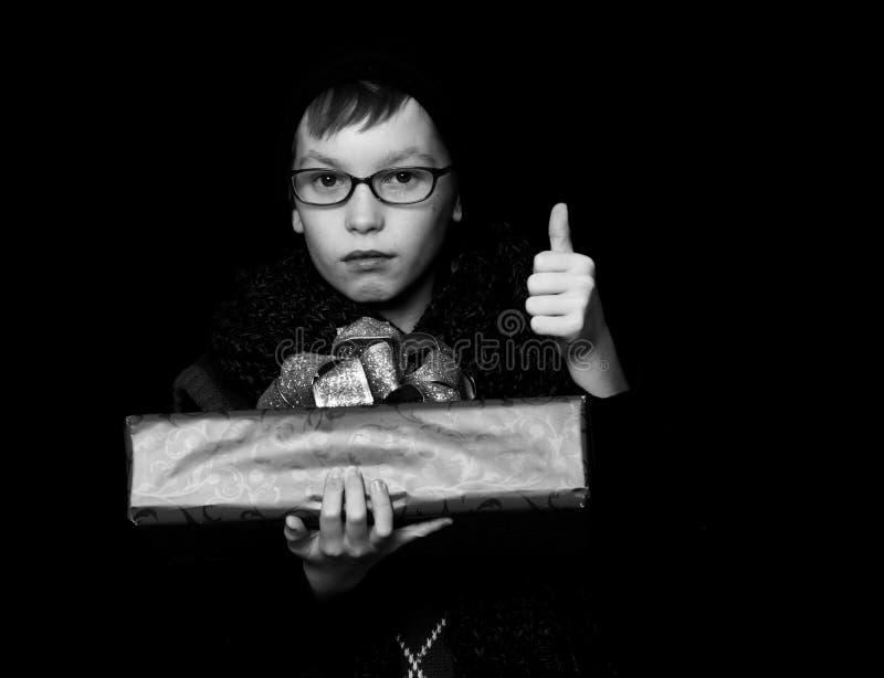 Il bambino piccolo o il bambino sveglio del nerd in vetri, cappello e sciarpa tricottata alla moda su fondo nero tiene la scatola immagini stock libere da diritti