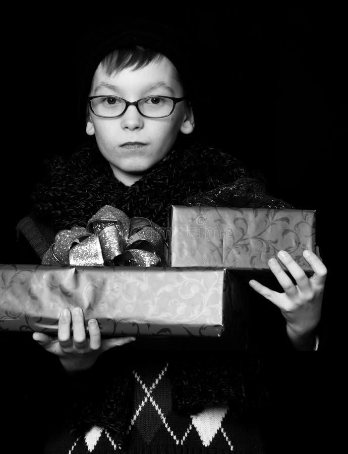 Il bambino piccolo o il bambino sveglio del nerd in vetri, cappello e sciarpa tricottata alla moda su fondo nero tiene le scatole fotografia stock