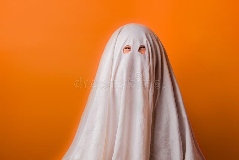 Il bambino piccolo si è vestito in un costume del fantasma per Halloween su fondo arancio immagini stock