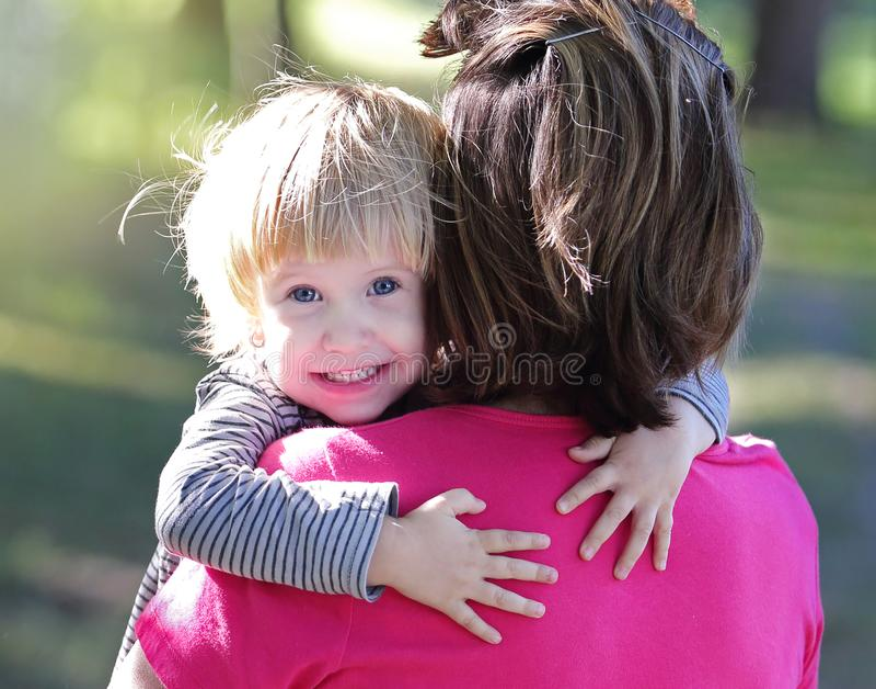 Il bambino piccolo sveglio abbraccia la sua mamma fotografia stock libera da diritti