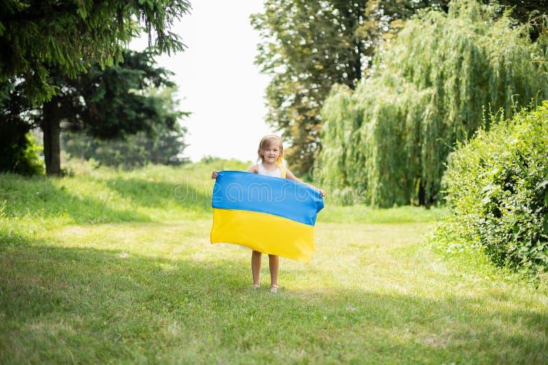 Il bambino porta l'ondeggiamento bandiera blu e gialla dell'Ucraina nel campo Festa dell'indipendenza del ` s dell'Ucraina Giorno fotografie stock libere da diritti