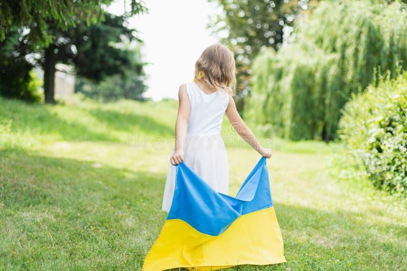 Il bambino porta l'ondeggiamento bandiera blu e gialla dell'Ucraina nel campo Festa dell'indipendenza del ` s dell'Ucraina Giorno fotografia stock