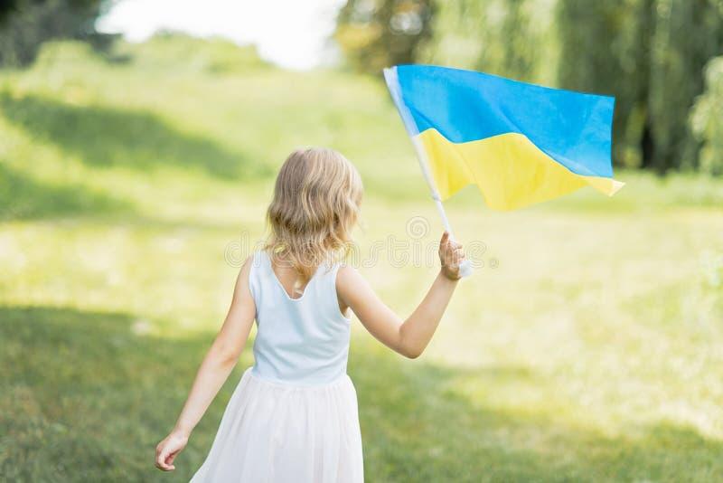 Il bambino porta l'ondeggiamento bandiera blu e gialla dell'Ucraina nel campo Festa dell'indipendenza del ` s dell'Ucraina Giorno fotografie stock