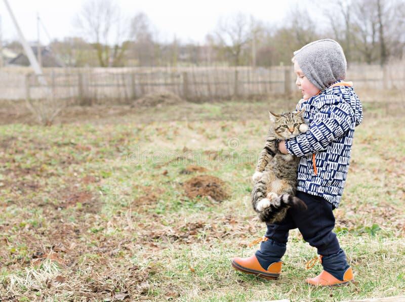 Il bambino porta un gatto nelle sue armi Copi lo spazio immagini stock