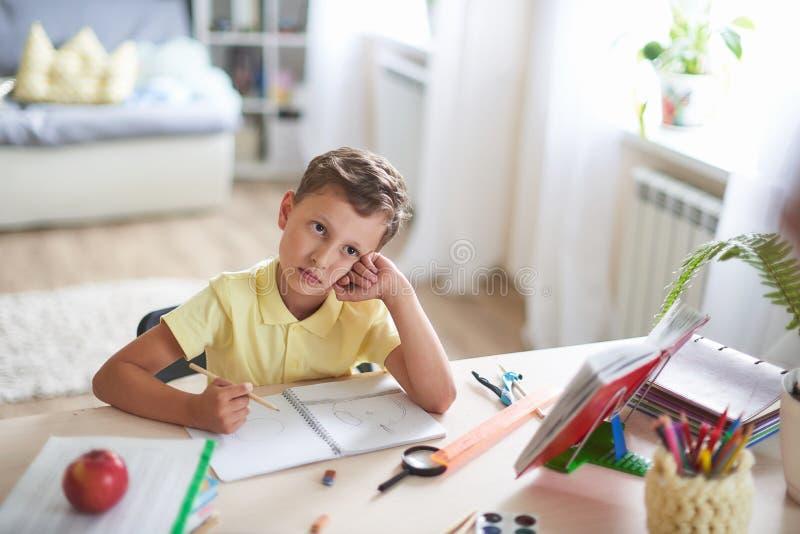 Il bambino premuroso si siede ad una tavola con i manuali ed i rifornimenti educativi sogni e sguardi dello studente alla cima at fotografie stock libere da diritti