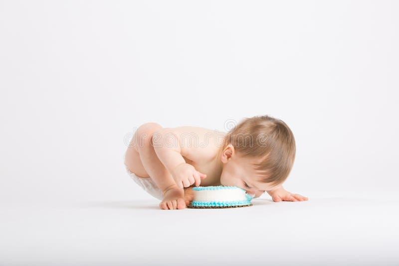 Il bambino prende un morso enorme del dolce con il fronte immagini stock