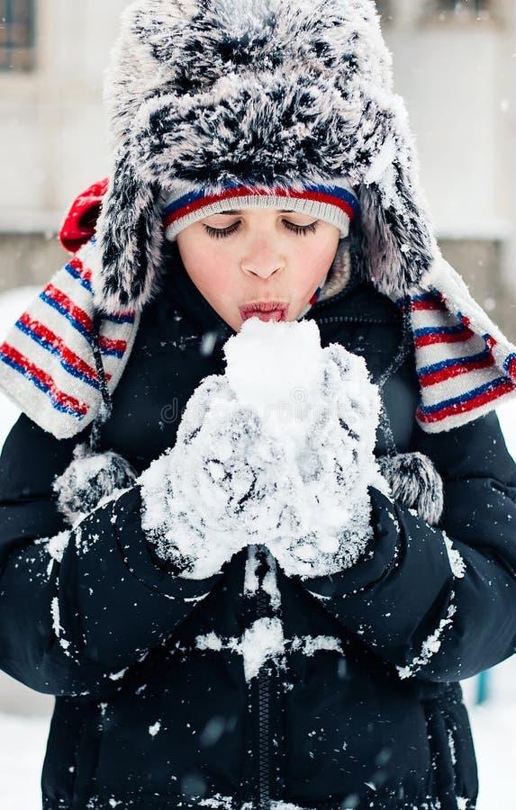 Il bambino prova il gusto di neve immagini stock
