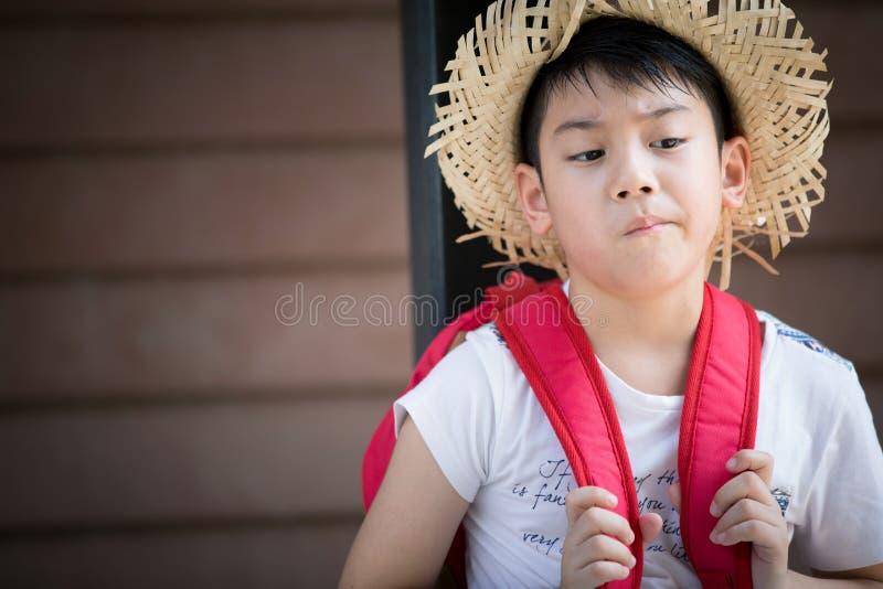 Il bambino rosso annoiato asiatico sta pensando mentre immagine stock