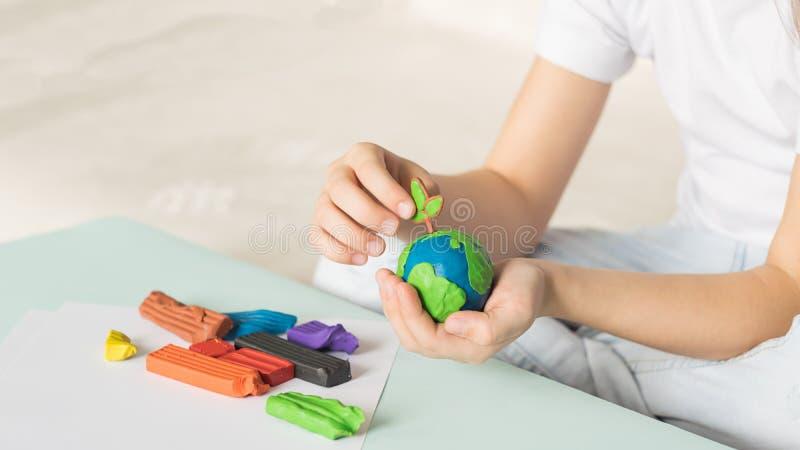 Il bambino scolpisce da plasticine il globo e gli alberi La posizione del pianeta in palme dei bambini Concetto di ecologia fotografie stock