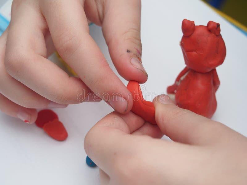 Il bambino scolpisce una figura da plasticine Children& x27; Cr artistico di s fotografia stock