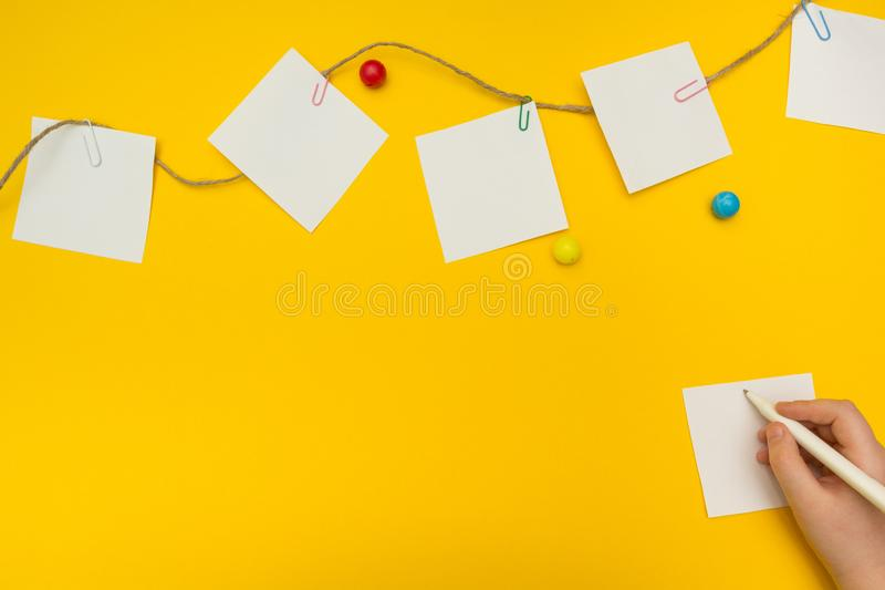 Il bambino scrive una nota su un fondo giallo Le note della carta fotografie stock libere da diritti