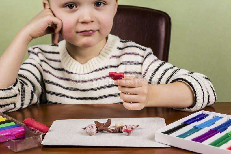 Il bambino sculpts da argilla fotografia stock