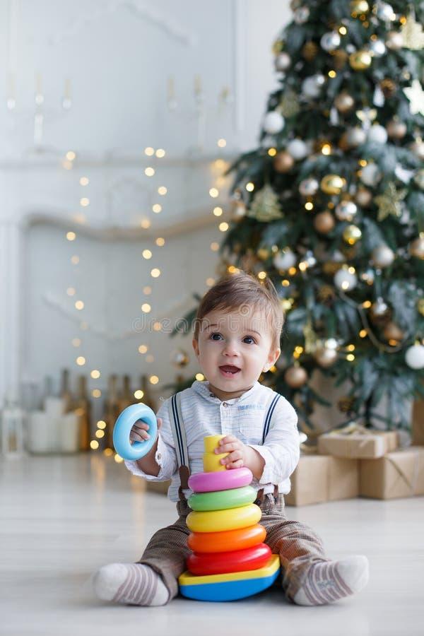 Il bambino, sedentesi sul pavimento vicino ad un albero di Natale astuto, raccoglie una piramide multicolore fotografia stock libera da diritti