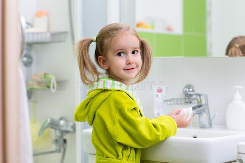 Il bambino si lava le sue mani al bagno Mani di lavaggio della ragazza con sapone fotografia stock