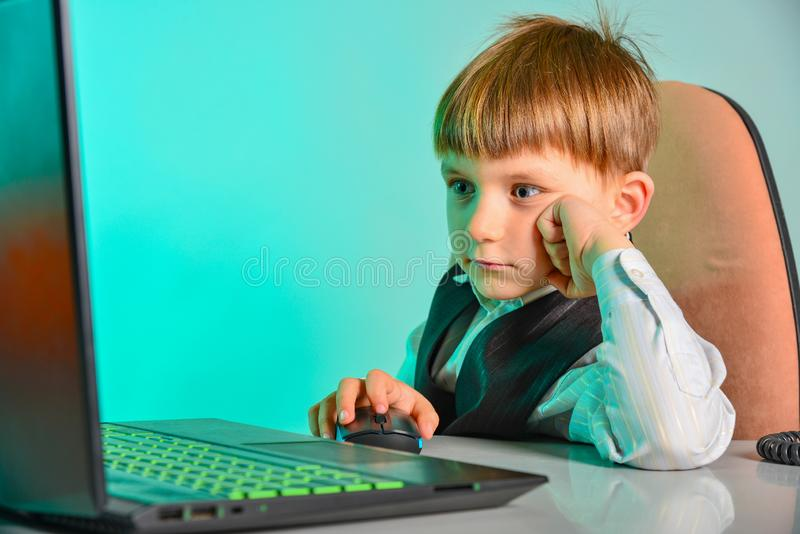 Il bambino si siede ad un computer portatile ed agli sguardi allo schermo di monitor fotografie stock