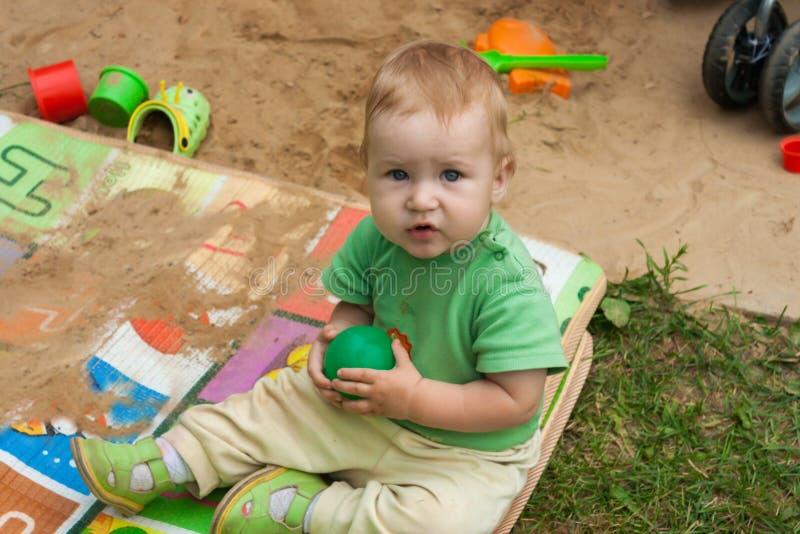 Il bambino si siede su una coperta dei bambini del poliuretano nella via fotografia stock libera da diritti