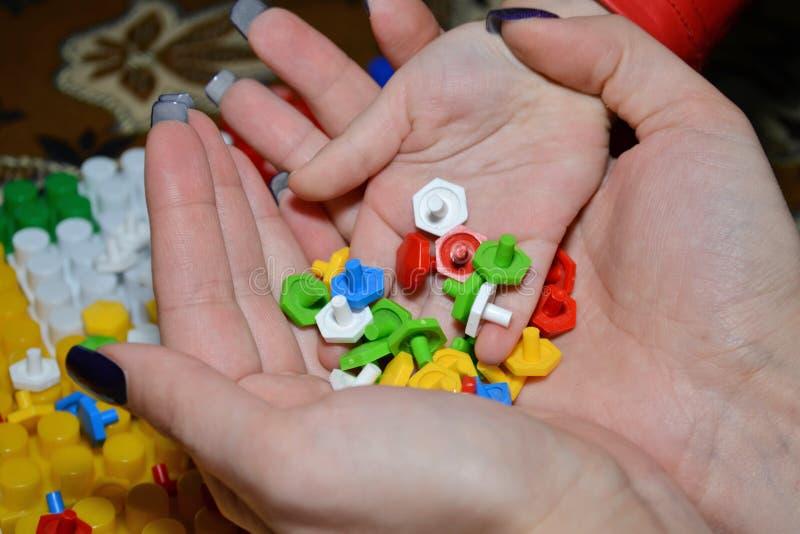 Il bambino si trasforma le mani dei pezzi della mamma di mosaici variopinti fotografia stock