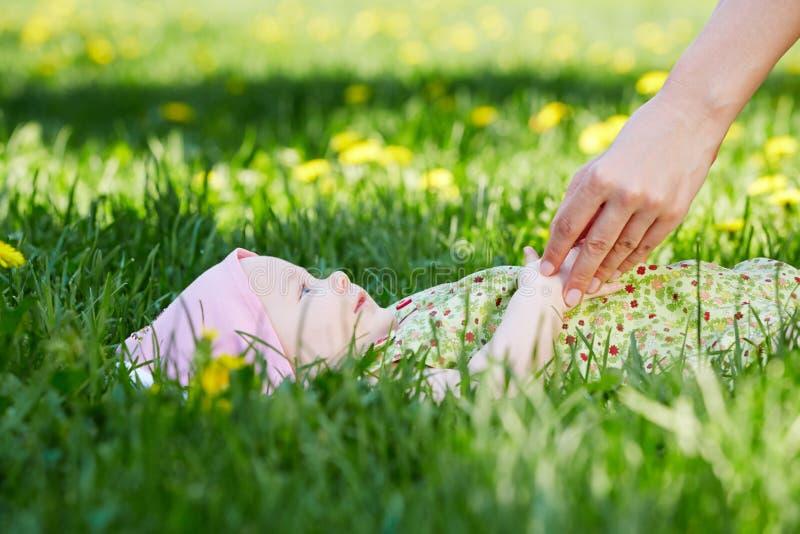 Il bambino si trova su erba, madre che la mano lo tocca fotografia stock libera da diritti