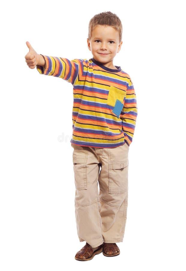 Il bambino sorridente con i pollici aumenta il segno fotografie stock