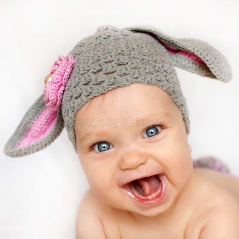 Il bambino sorridente gradisce un coniglietto o un agnello fotografia stock